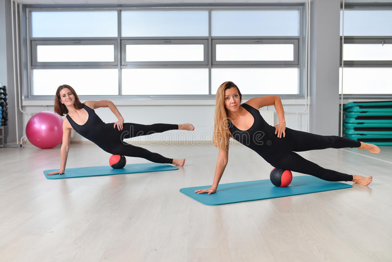 Fitness, sport, exercising lifestyle - fit women in bodysuit doing exercises with medicine ball at gym.  royalty free stock image