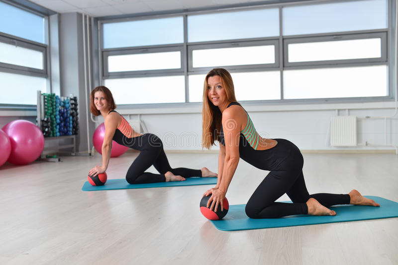 Fitness, sport, exercising lifestyle - fit women in bodysuit posing on mat with medicine ball at gym royalty free stock photo