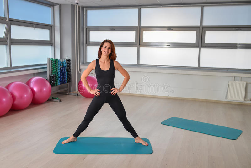 Fitness, sport, exercising lifestyle - Happy woman in bodysuit posing at gym.  stock images