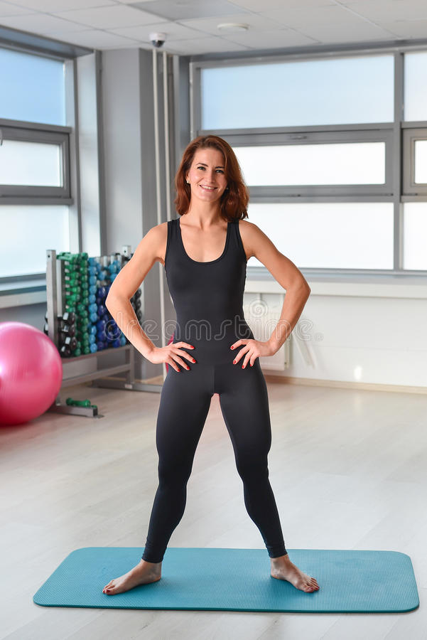 Fitness, sport, exercising lifestyle - Happy woman in bodysuit posing on yoga mat at gym.  stock image