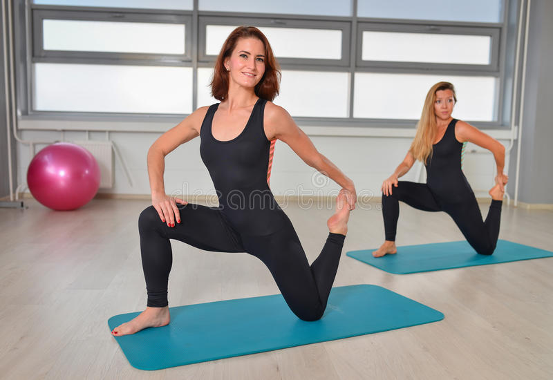 Fitness, sport, exercising lifestyle - Happy women stretching in gym royalty free stock photos