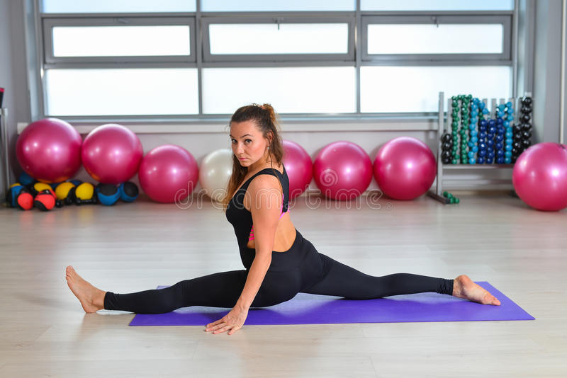 Fitness, sport, exercising lifestyle - middle aged woman in bodysuit doing splits exercise gym.  stock images