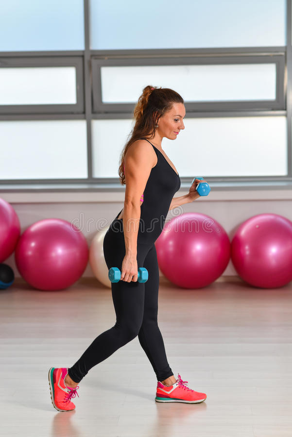 Fitness, sport, exercising lifestyle - middle aged woman in bodysuit working out with dumbbells at gym.  stock photos