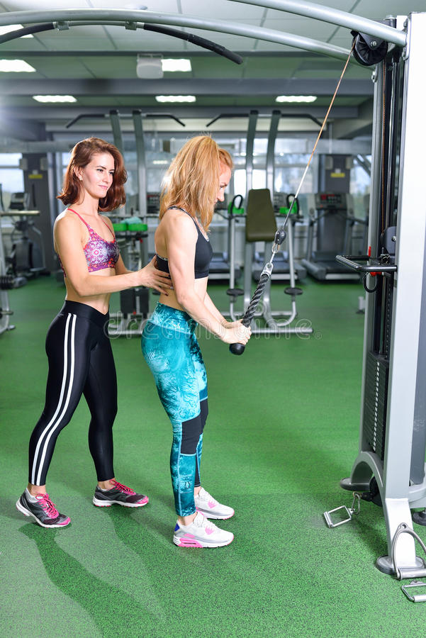 Fitness, sport, exercising lifestyle - personal trainer supporting his client while doing rope extension in gym.  stock image