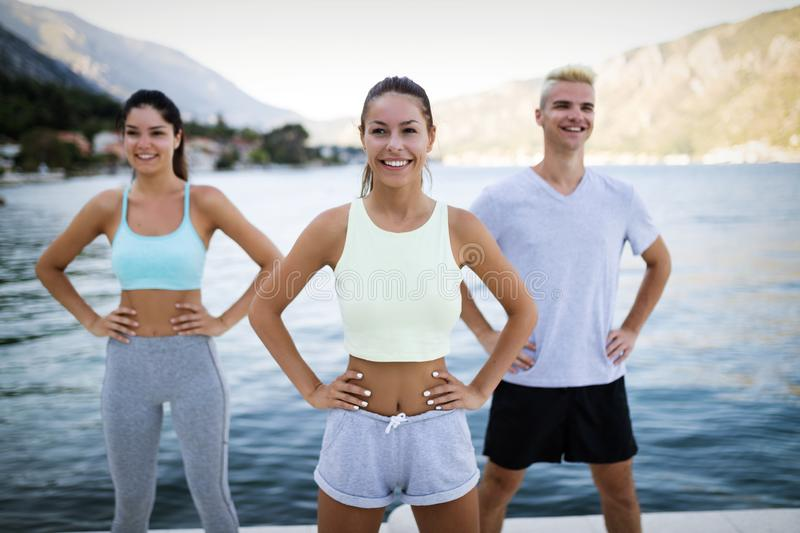 Group of happy friends or sportsmen exercising and stretching outdoor royalty free stock photography