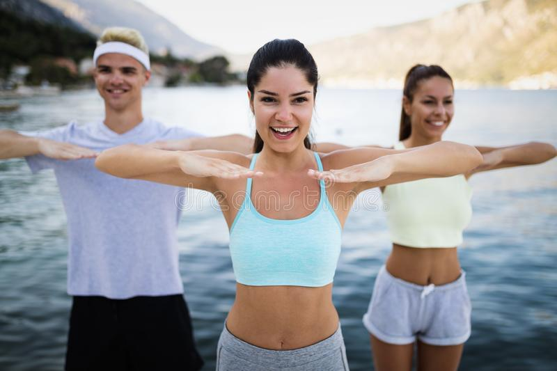 Group of happy friends or sportsmen exercising and stretching outdoor royalty free stock photo