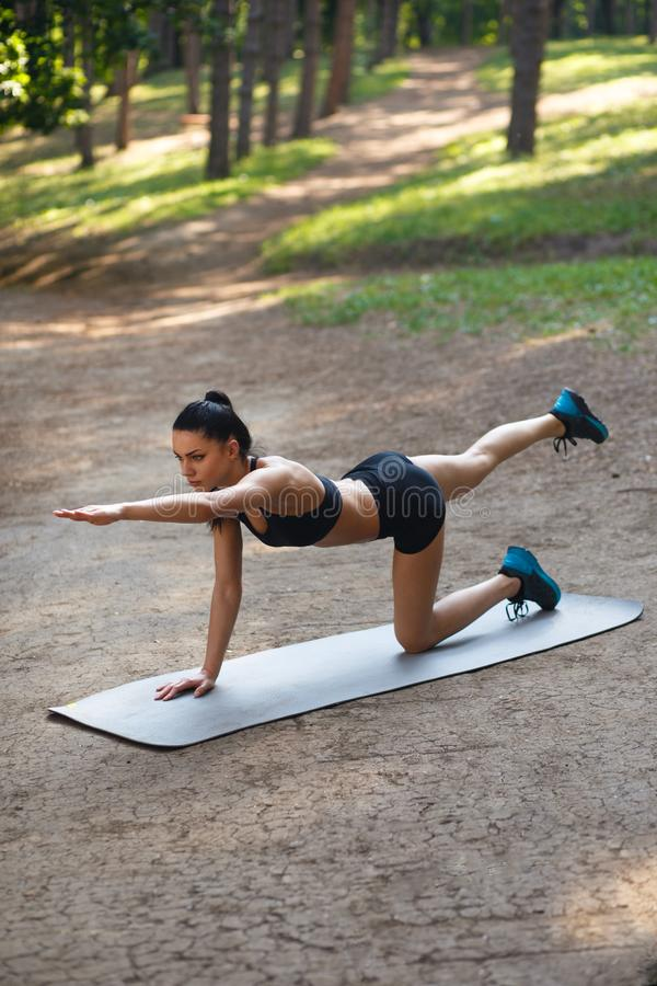 Fitness sport girl in fashion sportswear doing fitness exercise in the park. Outdoor workout in summer time. stock photography