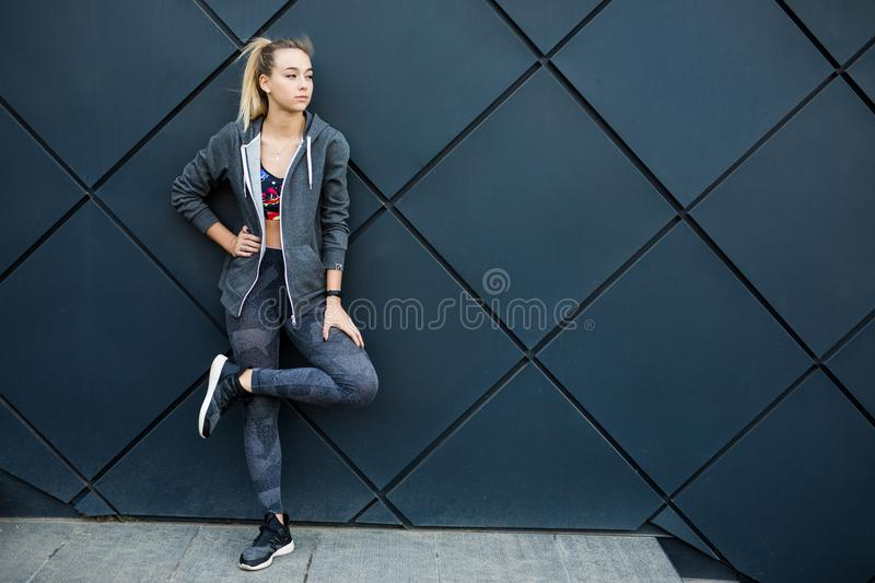 Fitness sport girl in fashion sportswear doing fitness exercise in the street, outdoor sports, urban style stock photography