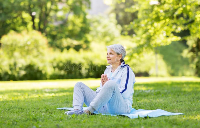 Happy senior woman doing yoga at summer park. Fitness, sport and healthy lifestyle concept - happy smiling senior woman doing yoga on exercise mat at summer park royalty free stock photo