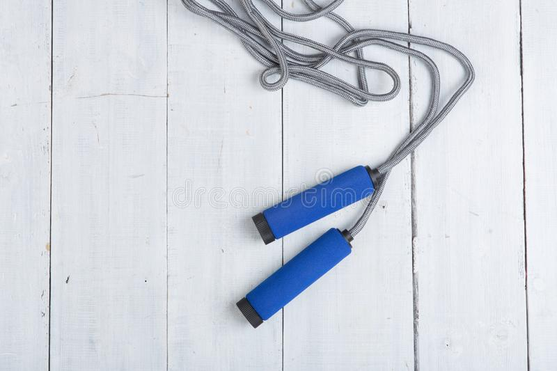Fitness/sport and healthy lifestyle concept - Jumping/skipping rope with blue handles stock photo