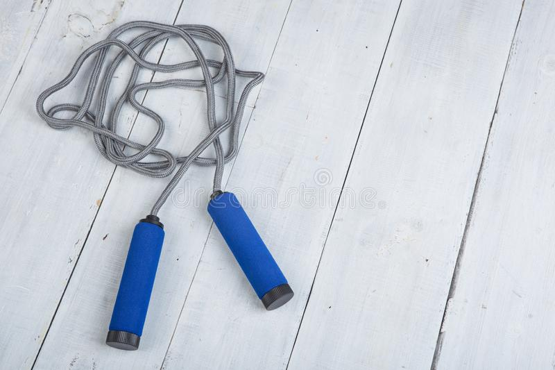 Fitness/sport and healthy lifestyle concept - Jumping/skipping rope with blue handles stock images