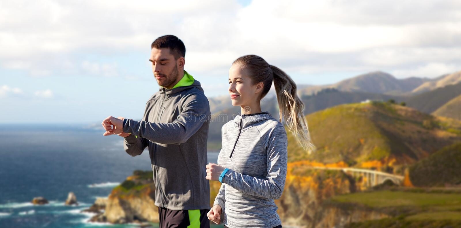 Couple with fitness trackers running outdoors stock image