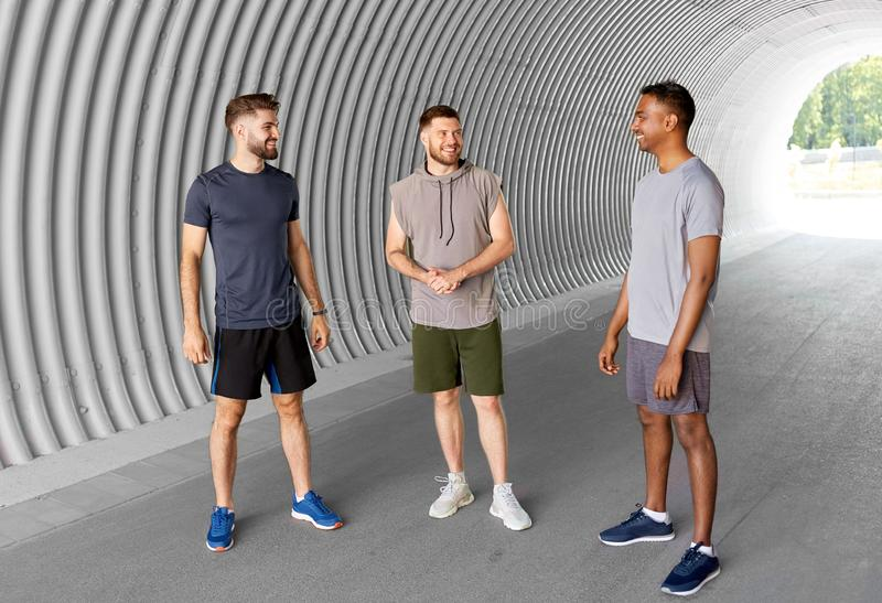 Young sporty men or male friends talking in tunnel stock images