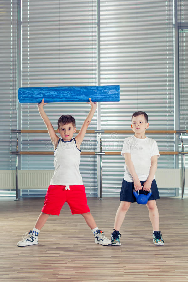 Fitness, sport, het concept van de opleidingslevensstijl - kinderen in de gymnastiekgewichten en met schuimrol stock foto