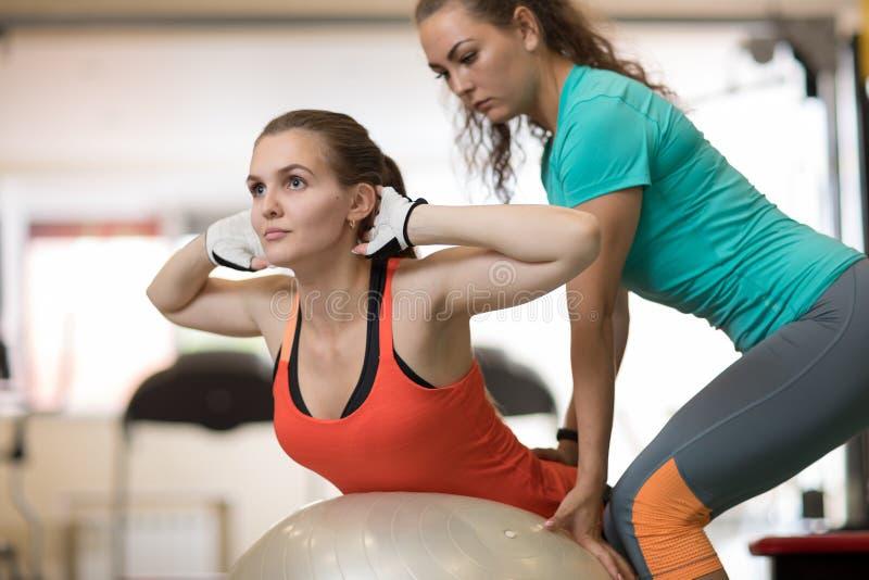 Fitness, sport, het uitoefenen en gezondheidsconcept - jonge vrouw en persoonlijke trainer in gymnastiek stock afbeeldingen