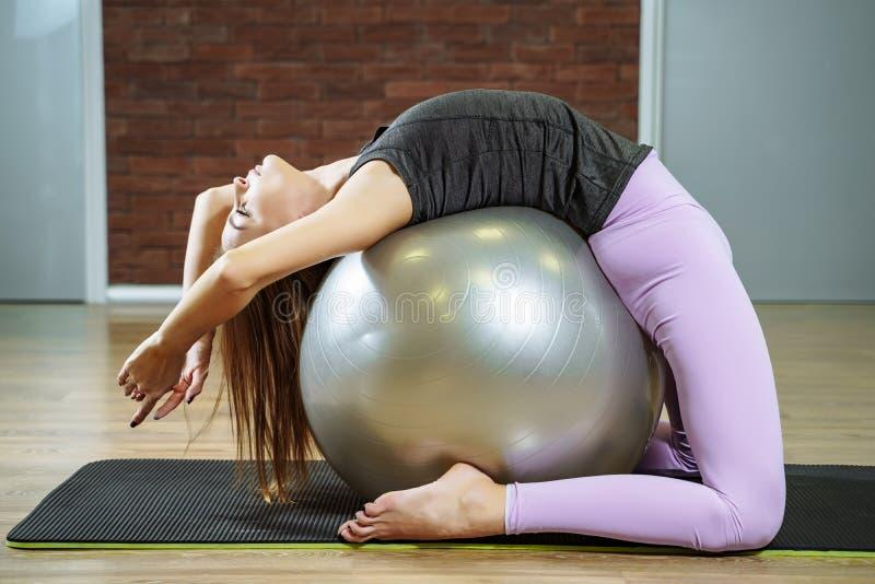 Fitness, sport, levensstijl - jonge vrouw die oefeningen met geschikte bal in een pilatesklasse doen royalty-vrije stock foto