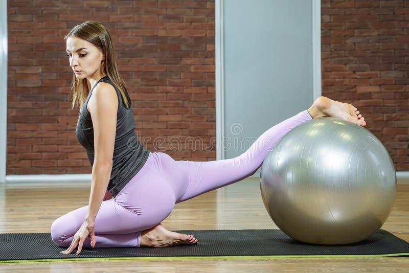 Fitness, sport, levensstijl - jonge vrouw die oefeningen met geschikte bal in een pilatesklasse doen stock foto's