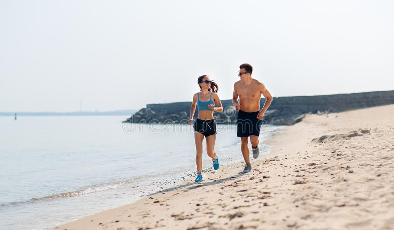 Couple in sports clothes running along on beach. Fitness, sport and lifestyle concept - happy couple in sports clothes and sunglasses running along summer beach royalty free stock photography