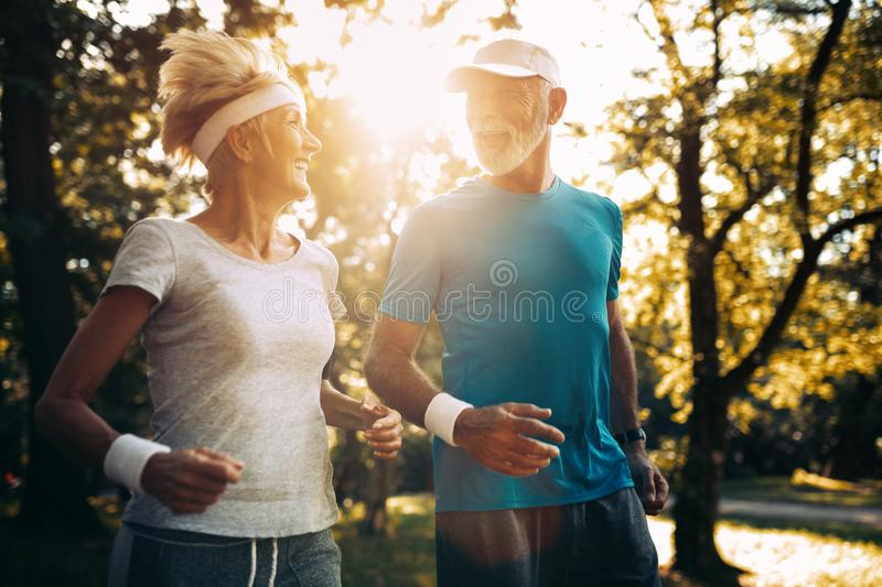 Fitness, sport and lifestyle concept - happy mature couple in sports clothes outdoors. Fitness, sport and lifestyle concept - happy senior couple in sports royalty free stock image