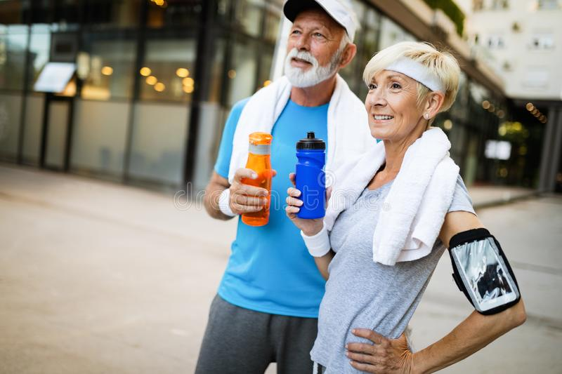 Fitness, sport and lifestyle concept - happy mature couple in sports clothes outdoors. Fitness, sport and lifestyle concept - happy senior couple in sports royalty free stock photography