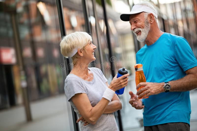 Fitness, sport and lifestyle concept - happy mature couple in sports clothes outdoors. Fitness, sport and lifestyle concept - happy senior couple in sports stock photo
