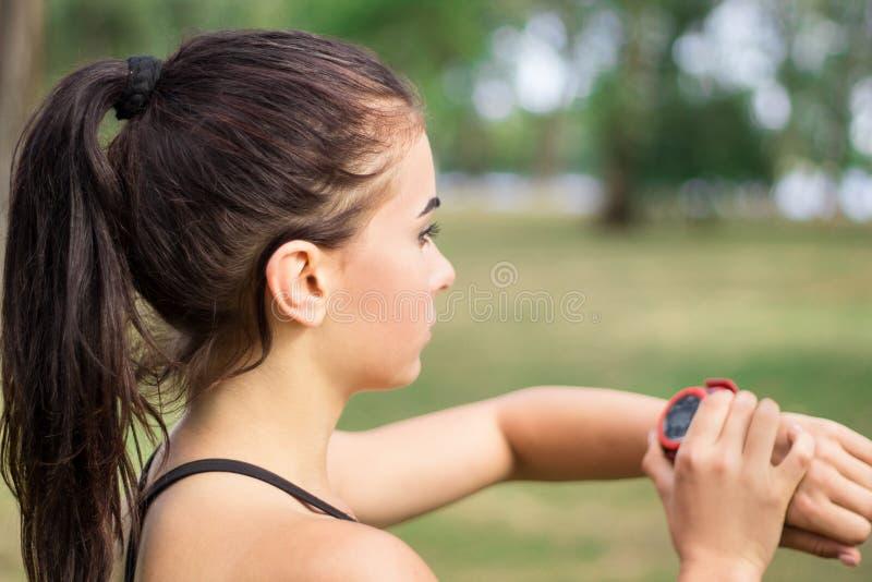 Fitness-Sport-Mädchen überprüft Timer während des Trainings lizenzfreies stockbild