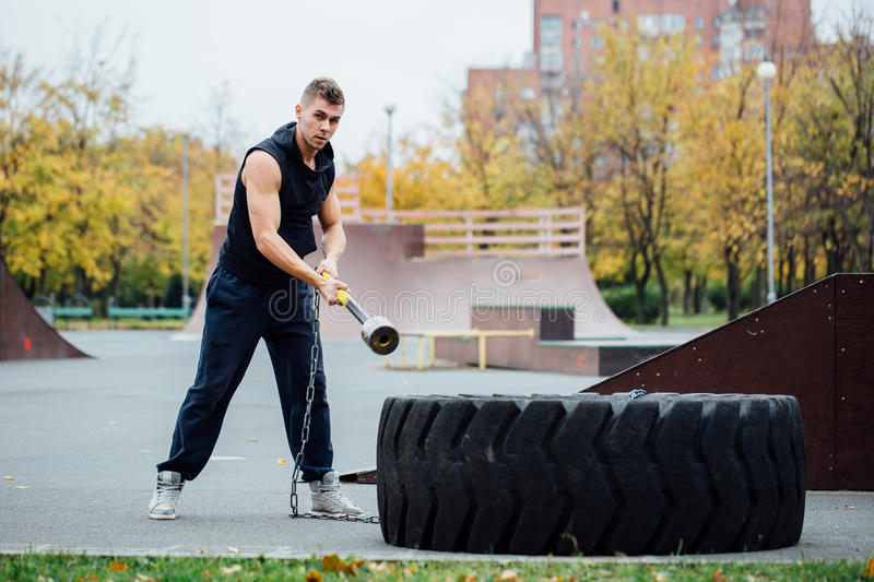 Fitness sport man workout outdoor. with hammer and tractor tire. royalty free stock images