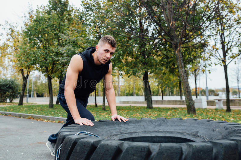 Fitness sport man workout outdoor. with tractor tire. stock images