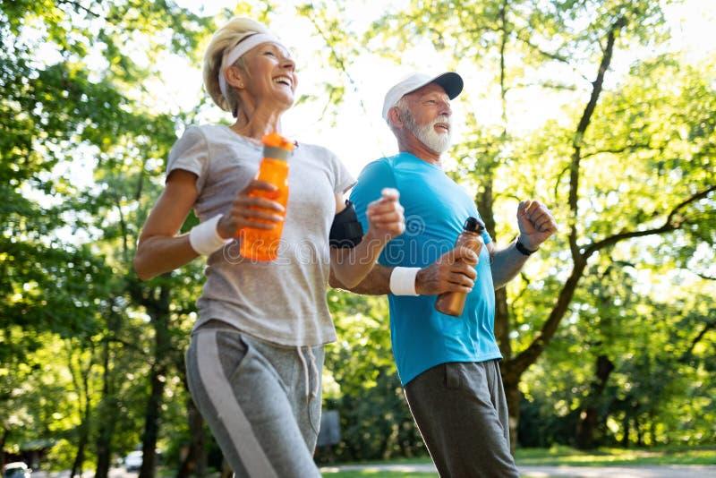 Fitness, sport, mensen, het uitoefenen en levensstijlconcept - het hogere paar lopen stock foto