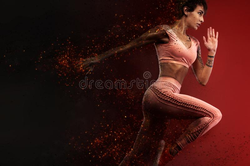 Fitness and sport motivation.. Strong and fit athletic, woman sprinter or runner, running on red background in the fire wearing sp royalty free stock images