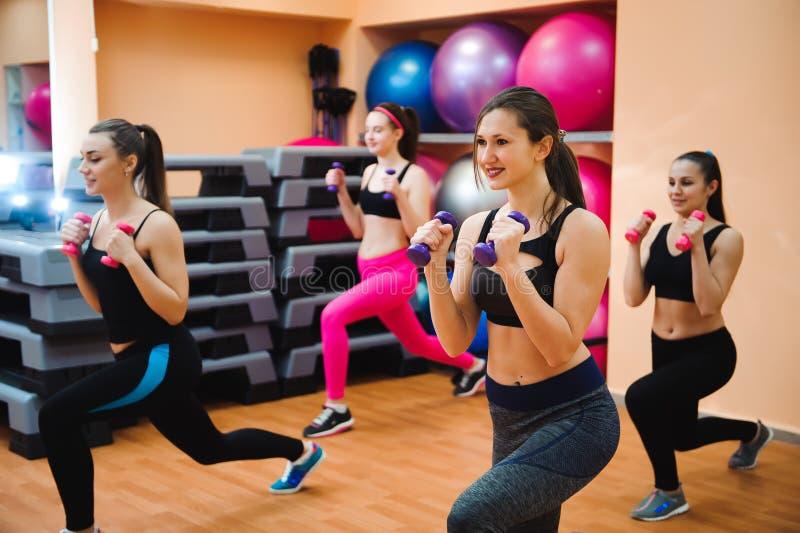 Fitness, sport, opleiding en levensstijl concept - groep gelukkige vrouwen met domoren die spieren in gymnastiek buigen stock afbeelding