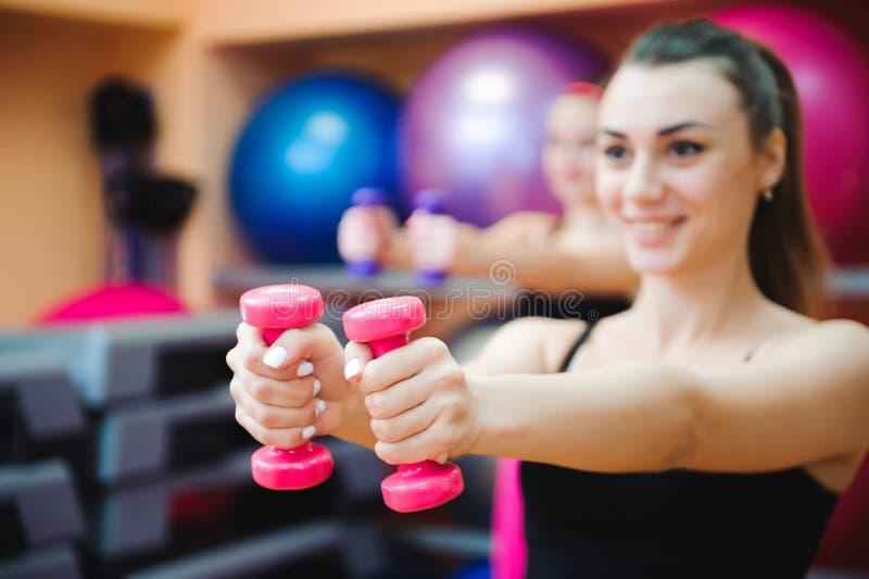 Fitness, sport, opleiding en levensstijl concept - groep gelukkige vrouwen met domoren die spieren in gymnastiek buigen royalty-vrije stock foto's