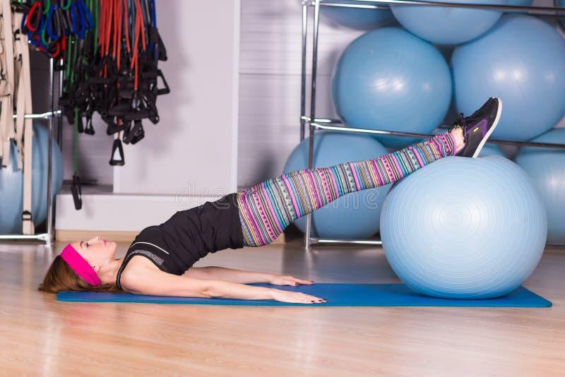 Fitness, sport, opleiding en levensstijl concept - het glimlachen de bal van de vrouwenoefening in gymnastiek stock afbeeldingen