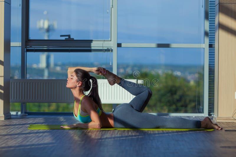 Fitness, sport, opleiding en levensstijl concept - het glimlachen vrouw het uitrekken zich op mat in gymnastiek licht van een gro stock foto