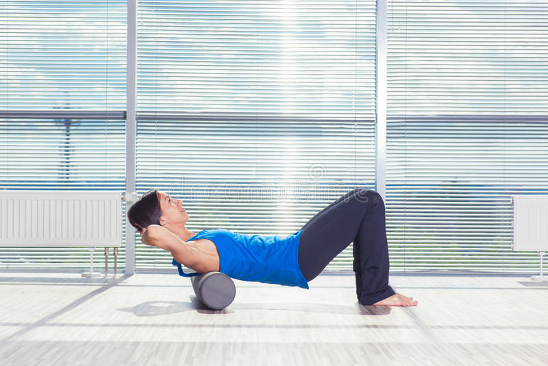 Fitness, sport, opleiding en levensstijl concept - vrouw die pilates op de vloer met schuimrol doen royalty-vrije stock afbeelding