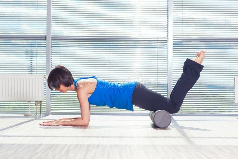 Fitness, sport, opleiding en levensstijl concept - vrouw die pilates op de vloer met schuimrol doen royalty-vrije stock foto
