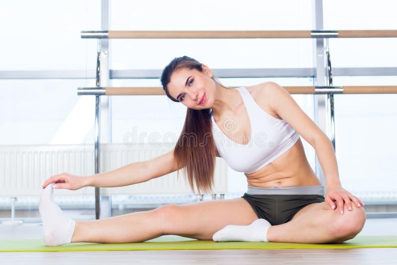 Fitness, sport, opleiding en mensenconcept - Gelukkige jonge vrouw die alvorens in gymnastiek te lopen uitrekken zich stock foto's