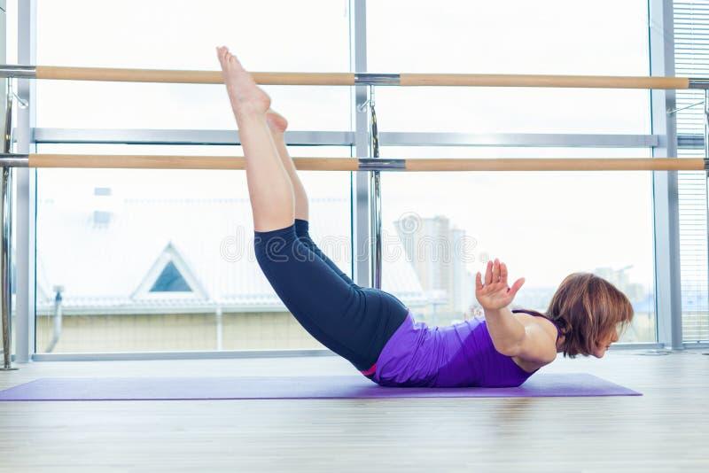 Fitness, sport, opleiding en mensenconcept - glimlachende vrouw die buikoefeningen op mat in gymnastiek doen stock foto