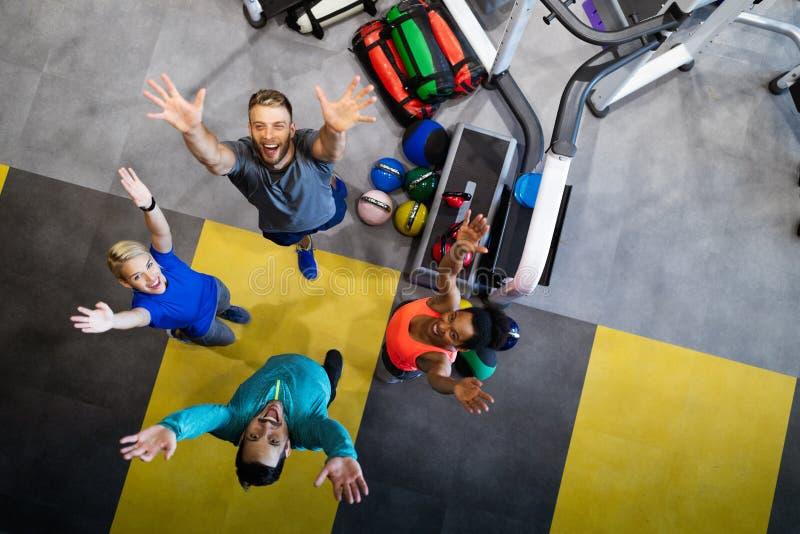 Fitness, sport, opleiding, gymnastiek, succes en levensstijl Groep gelukkige vrienden in de gymzaal stock afbeelding