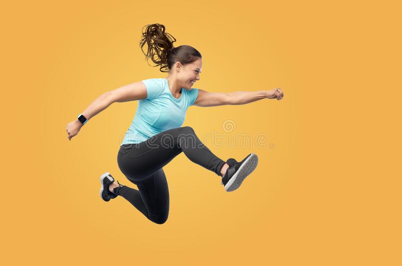 Happy fit young woman jumping in air royalty free stock images