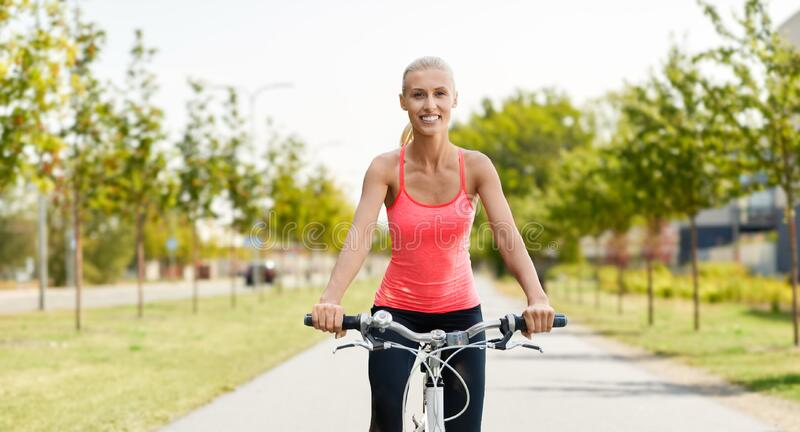 Happy young woman riding bicycle outdoors stock photography