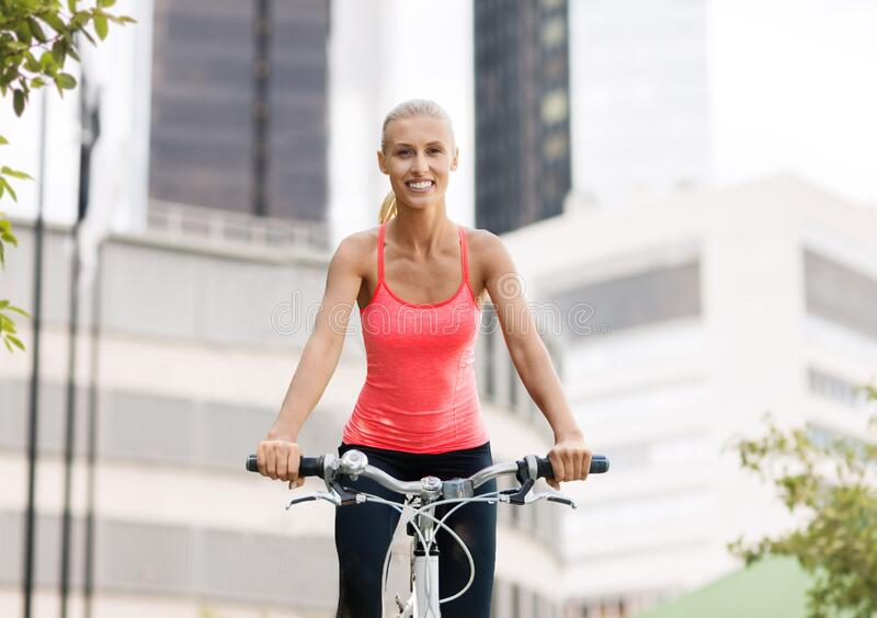 Happy young woman riding bicycle at city stock photo