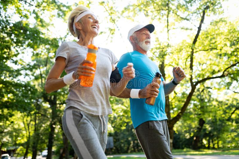 Fitness, sport, people, exercising and lifestyle concept - senior couple running stock photo