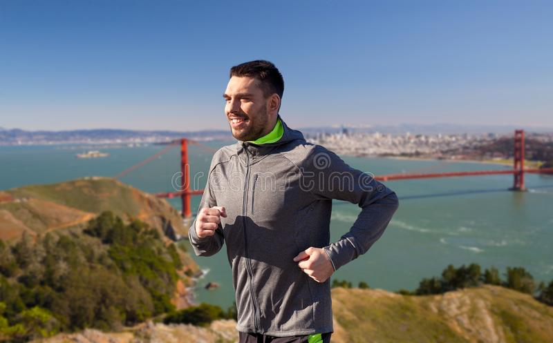 Happy young man running over golden gate bridge royalty free stock images
