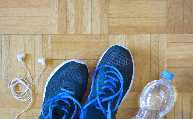fitness, sport, running and reducing weight, pair of runners and earphones and water royalty free stock photo