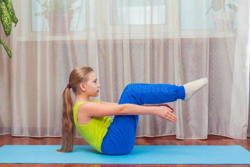 Fitness. sport, training and lifestyle concept - Child doing exercises on mat in home. stock photos