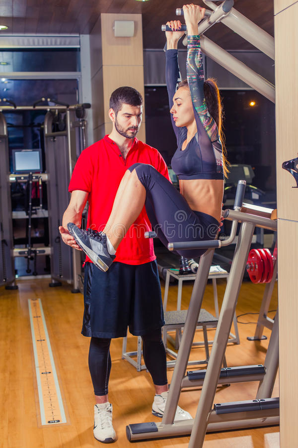 Fitness, sport, training and people concept - Personal trainer helping woman working with abdominal muscles press on the stock photo