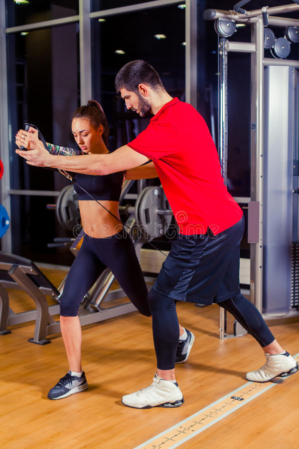 Fitness, sport, training and people concept - Personal trainer helping woman working with in gym royalty free stock photo