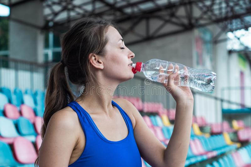 Fitness sport woman in fashion sportswear, the girl is drinking water, fitness exercise in the city street royalty free stock photos