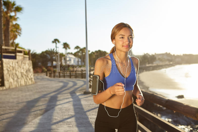 Fitness sport woman running on the beach shore royalty free stock photography